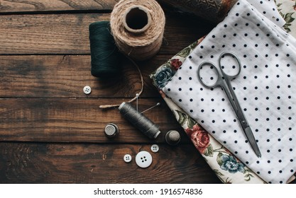 Needlework concept. Various sewing tools. Needles, scissors, buttons, spools, threads of different colors. Sewing accessories and fabric. Sewing threads, needles, pins, fabric on a wooden background.