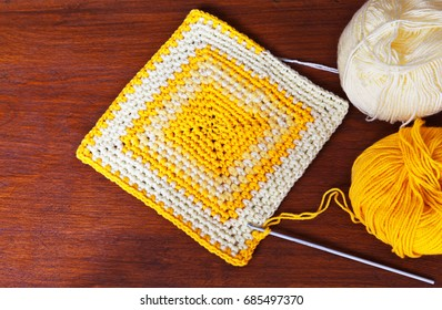 Needlework. Crocheted striped square and skeins of yellow acrylic yarn on a wooden background