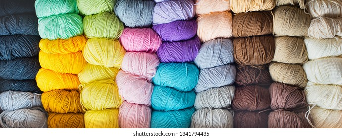 Needlework and crocheting and knitting. Colorful multicolored skeins. Yellow, blue, pink, milk, beige, gray, purple, lilac yarn.Women's hobby. Banner