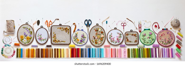 Needlework and embroidery. Panoramic top view of different types of embroideries with satin ribbons.