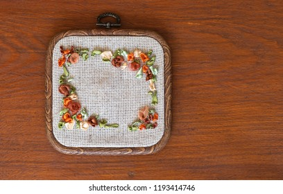 Needlework. Embroidery with satin ribbons in square hoop on a wooden table (These pictures of embroidery and embroidery with satin ribbons were performed by the author of the photo)