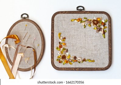 Needlework and hobbies. Hand embroidery with satin ribbons of a floral square ornament in a frame. Needles with colored ribbons on oval hoop on white table (embroidery made by the author of the photo)
