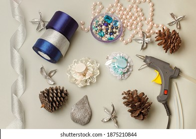 Needlework lessons.Tapes,cloth, glue gun.Hat hair clip.Crafts.DIY. Shiny ribbon,cones,handcraft tool, ribbon beads on a gray background.Winter crafts. Quarantine session.Handmade.