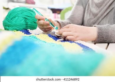 Needlework. The woman knits crochet.