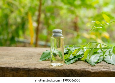 Neem oil in bottle and fresh neem leaf on wooden and blur background on sunny day.