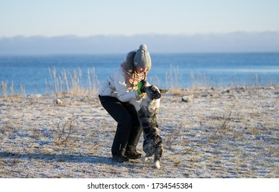 Neeme / Estonia - January 14 2018: Teenager girl in white jacket doing obedience exercises with welsh corgi cardigan dog next to frozen sea ice. Eager dog standing on her rear  paws. Winter landscape.