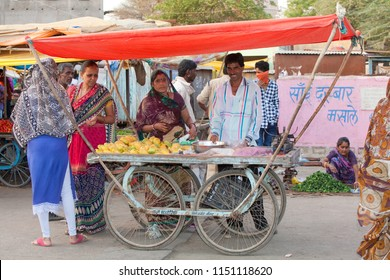 Neemuch, India - April 30, 2016: indian woman in traditional sari and man stand behind a sales cart on the market and offer mangoes, a few other women in traditional dresses stand around