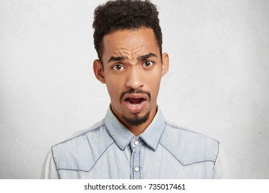 Negative emotions and body language concept. Unsatisfied black man frowns face and looks with opened mouth, feels puzzled as lost in unknown place, asks for way in passers by, isolated over white wall