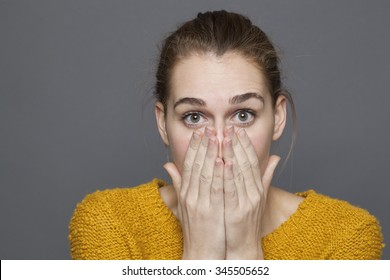 negative feelings concept - shocked beautiful 20s girl covering her mouth and nose with hands for emotions or bad odor,studio shot on gray background