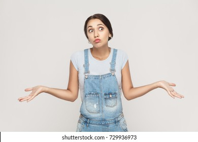 Negative human emotions, facial expressions. Puzzled  young adult woman with arms out, shrugging her shoulders, saying: who cares, so what, I don't know. Isolated studio shot on gray background.