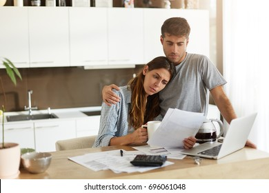 Negative human emotions. Financial problems. Portrait of unhappy young couple having looking worried while reading notification informing them about eviction from appartment because of unpaid bills