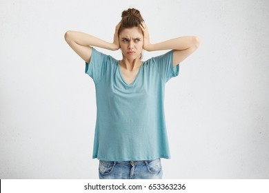 Negative human emotions, reaction and attitude. Frustrated annoyed student girl with hair knot covering ears with hands, feeling irritated with loud annoying noise, can't concentrate on her homework