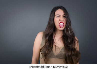 Negative human expressions and attitude. Dissatisfied female has disgusting expression shows tongue as sees something not appealing, frowns face, isolated over white  background. Distaste and dislike