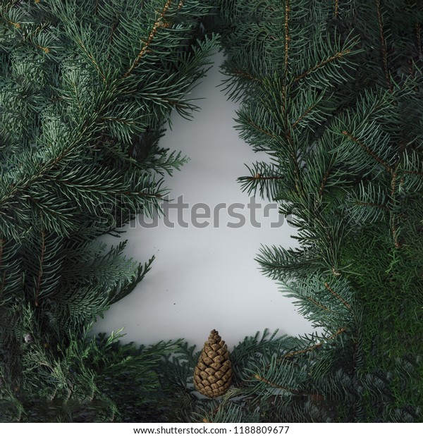 Negative space Christmas tree concept. Creative winter layout made with evergreen tree branches. Flat lay.