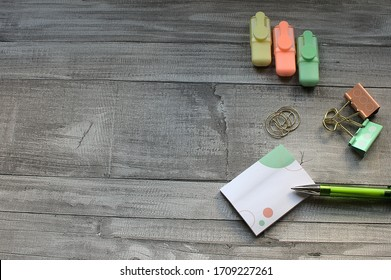 Negative space, concept work at home. notepad and green pen, next there is paper clips and highlishters, on wooden table