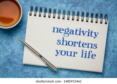 negativity shortens your life - inspirational handwriting in a  spiral art sketchbook against blue textured bark paper with a cup of tea