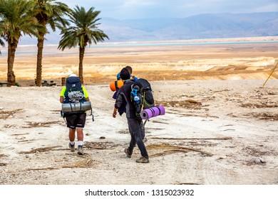 Negev, Israel- 01.08.2019: Group backpackers people traveling descending desert trail stone cliffs, hiking mountains Negev Israel, t