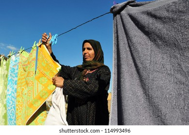 NEGEV, ISRAEL - NOVEMBER 26 2008:Bedouin woman hanging clothes .Nomadic Arabs live by rearing livestock in the Negev deserts in southern Israel.