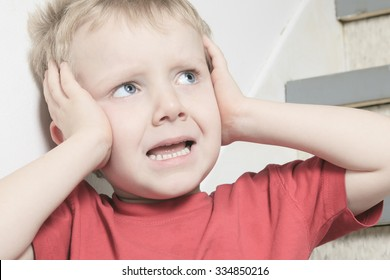 A Neglected lonely child leaning at the wall ear close with his hand