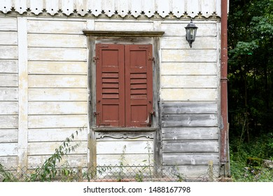 neglected old house with brown closed wooden shutters on window
