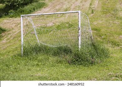 Neglected soccer goal on an uncut grass