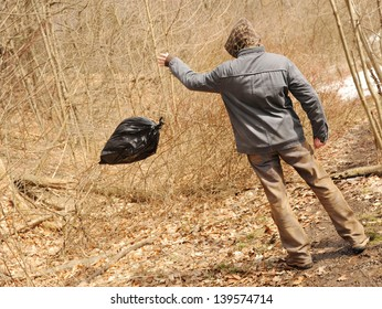Neglectful man throwing out the garbage in the forest