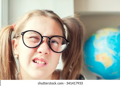 Neglecting the school. Nerdy funny girl with ponytails in eyeglasses. Indoors vibrant closeup horizontal image.