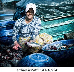 Negombo, Sri Lanka - 13 jan,2020: middle age sri lankan woman cleaning fish at fish market at Negombo. Daily work of worker at fish market.