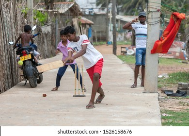 NEGOMBO, SRI LANKA - AUGUST 23, 2019 : Boys playing a game of cricket adjacent to Negombo beach in Sri Lanka.