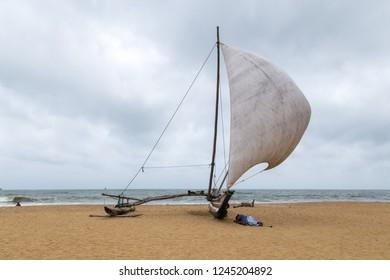 Negombo, Sri Lanka - July 25, 2018: Man sleeping next to a traditional catamaran fishing boat on the beach