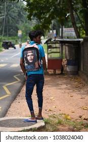 NEGOMBO,SRI LANKA - JANUARY 16.2018:unidentified boy waiting for a bus on January 16,2018 in Negombo, Sri Lanka