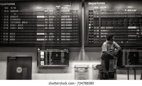 NEGOMBO,SRI LANKA - JUNE 14,2016 : A man waiting near Travel arrivals departure airport flip board in Bandaranaike international airport ,Sri Lanka ,Black and White tone
