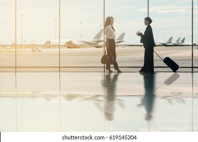 Negotiating business, Advertise, Travel,Traveling abroad concept - Two asian businesswoman talking and meeting at airport terminal on background blurred many airplanes on runway. (vintage color tone)