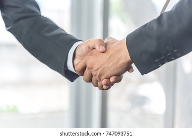 Negotiating business succeed, business people shaking hands at the working place.