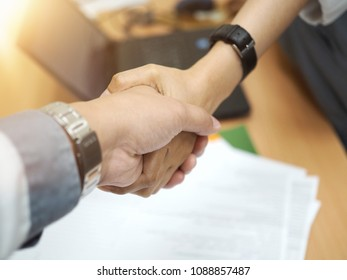 Negotiating business,Image of women Handshaking with a man,happy with work,the woman she is enjoying and congratulation with her workmate. Gesturing People Connection Deal Concept