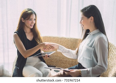 Negotiating business,young Asian businesswomen handshakes together