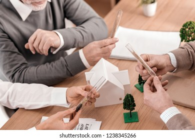 Negotiating. Determined skilled ecologists sitting at the table and holding beakers