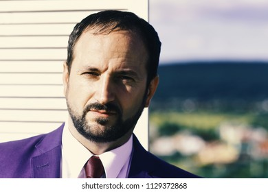Negotiation and business concept Businessman wears smart suit and tie on wooden wall and nature background. Leader with beard and serious face thinks about business. CEO searches for compromise.