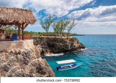 Negril, Jamaica, Caribbean rocky beach with turquoise water, tourists boat and lighthouse.