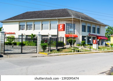 Negril, Jamaica - February 15, 2019: Bank of Nova Scotia (Scotiabank) in Westmoreland, Jamaica. Caucasian man standing outside 24 hour Automatic Teller Machine (ATM)/ Automated Banking Machine (ABM).