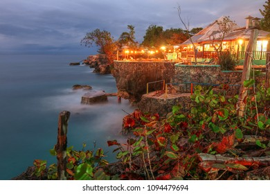 Negril, Jamaica - January 7 2018: Twilight at 3 Dives point in Negril, Jamaica. The rocky outcrops are very popular for cliff jumping and the location is renown for watching the sunset.