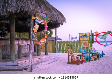 Negril, Jamaica - March 24 2018: Jimmy Buffett's Margaritaville on tropical Caribbean island Seven Mile Beach just after morning sunrise. Thatch roof bar and wooden lounge chairs on white sand setting