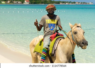 Negril, Jamaica - May 30 2015: Jamaican man riding horse along beach giving thumbs up wearing hat and colorful socks in Negril.