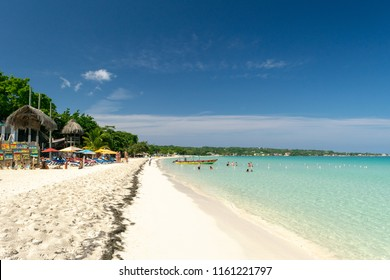 Negril, Jamaica - May 30 2015: Tourists at the Seven Mile Beach in Negril Jamaica on a sunny summer vacation day. Beautiful tropical island Caribbean beach scene.