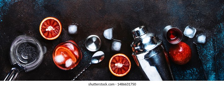 Negroni alcoholic cocktail beverage with dry gin, red vermouth and red bitter, bloody orange slice and ice cubes. Brown bar counter background, steel bar tools, top view, with copy space