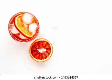 Negroni alcoholic cocktail with dry gin, red vermouth and red bitter, bloody orange slice and ice cubes. White background, steel bar tools, top view, copy space