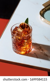 Negroni cocktail, with charred lemon and sage leaf, on a small table. Vintage aesthetic