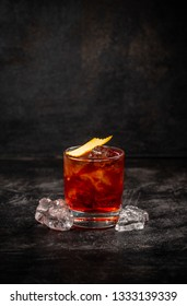 Negroni cocktail decorated with orange peel on dark background