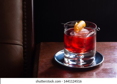 Negroni Cocktail, with Gin, Red Vermouth, and Campari, over Ice with Orange Twist in Dark Luxurious Bar with Copy Space