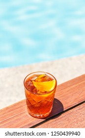 Negroni cocktail  near a pool at the resort bar or suite patio. Luxury resort, vacation, room service concept. Vertical